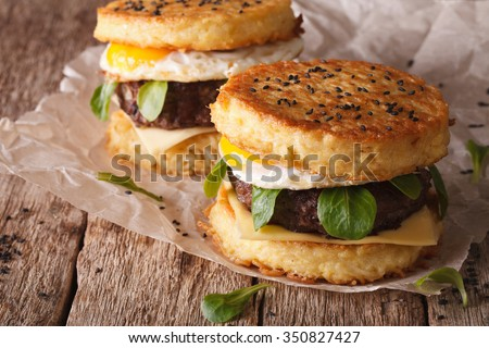 New fast food: ramen burger close-up on a paper on the wooden table. horizontal - stock photo