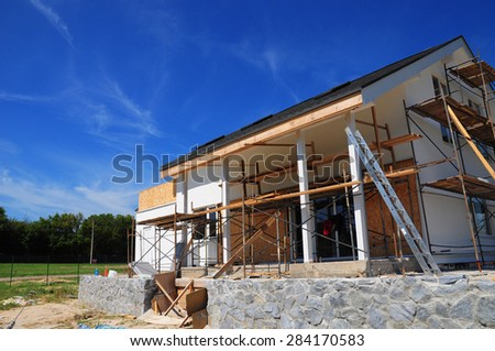 New frame house under construction against blue sky - stock photo