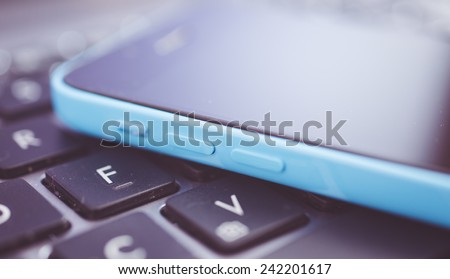 new generation smart phone lying on the computer keyboard - stock photo