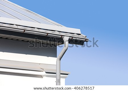 new gray metal rain gutter on house rooftop against blue sky - stock photo