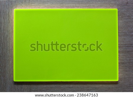 New green plastic plate with empty textspace on wooden background. - stock photo