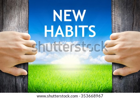 """New Habits. Hand opening an old wooden door and found wording """"New Habits."""" over green field and bright blue Sky Sunrise. - stock photo"""