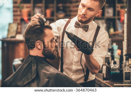 New hairstyle. Side view of young bearded man getting groomed at hairdresser with hair dryer while sitting in chair at barbershop - stock photo