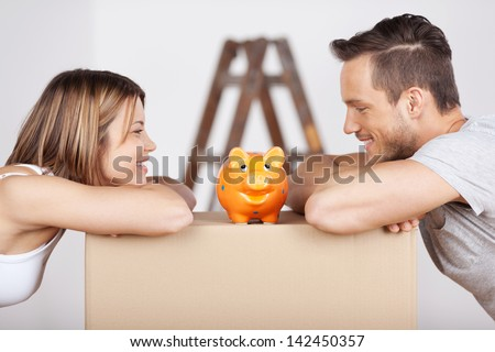 New happy couple looking at the piggybank in a savings concept - stock photo