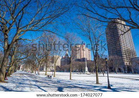 New Haven Green with snow and blue sky: a park in downtown New Haven, CT used for public events and bordered by Yale University. - stock photo
