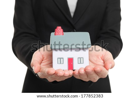 New Home and house owner concept. Woman holding a model house. Conceptual of home insurance and protection or real estate agent selling houses. Isolated on white background. - stock photo