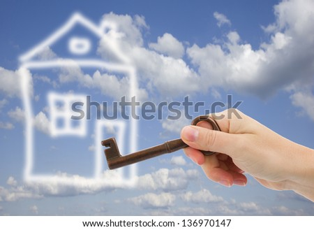 new home concept   - hand with key opens abstract home - stock photo