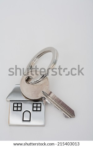 New home owner mortgage key and keyring laying on a white desk, close up view. Still life representation of home buying and mortgage commitment, interior. - stock photo