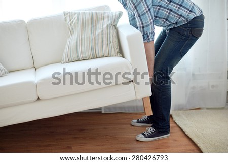 new home, real estate, moving and furniture concept - close up of male lifting up sofa or couch - stock photo