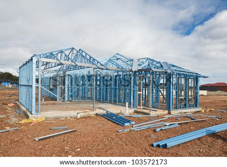New home under construction using steel frames against cloudy sky - stock photo