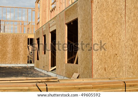 New Home Under Construction with Blue Sky and White Clouds - stock photo