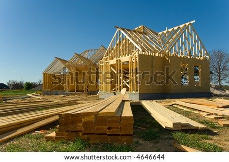 New home under construction with wood, trusses and supplies against blue sky - stock photo