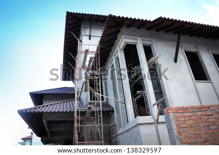 New house under construction against blue sky. - stock photo