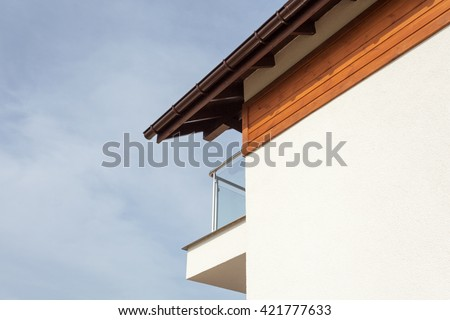 New house with brown rain gutter, white wall and balcony - stock photo