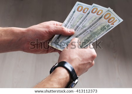 new hundred dollar banknotes in man's hands - stock photo