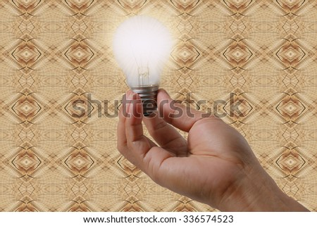 New idea concept with wood background, man hand holding light bulb - stock photo