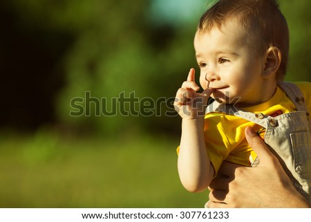 New life born concept. Portrait of cute baby boy sitting in dad's hands and smiling over green forest background. Sunny summer day. Close up. Copy-space. Outdoor shot - stock photo