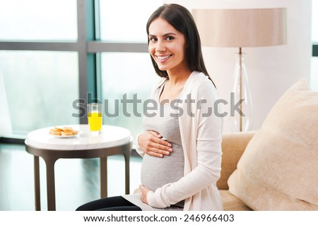 New life inside me. Side view of beautiful young pregnant woman touching her abdomen and smiling while sitting on the couch near the table with orange juice and cookies on it  - stock photo