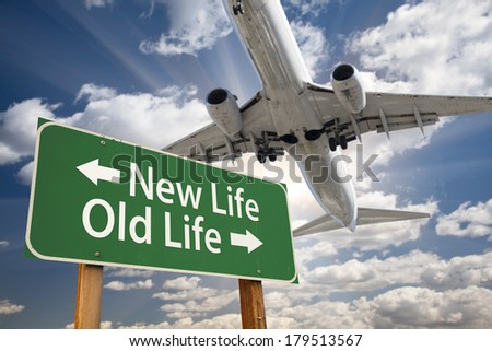 New Life, Old Life Green Road Sign and Airplane Above with Dramatic Blue Sky and Clouds. - stock photo