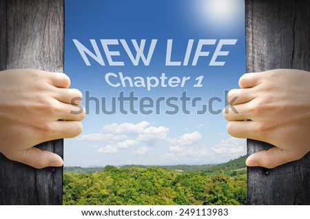New life word floating on the sky behind 2 hands trying to open a wooden door. - stock photo