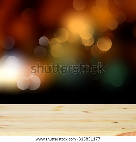 New light pine wooden deck table with a sparkling bokeh of party lights in the black background - stock photo