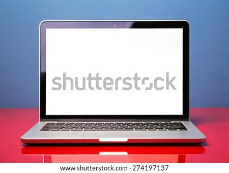 New modern laptop closeup on red modern desk - stock photo