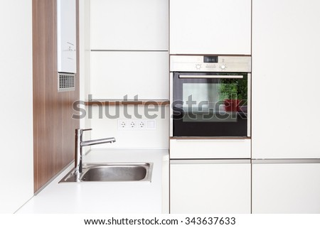 New modern white kitchen with built in oven and chrome water tap - stock photo