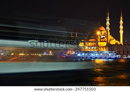 New Mosque at Istanbul in night time with lights of boats pasing by Golden Horn bay - stock photo