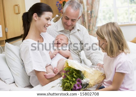 New mother with baby and family in hospital smiling - stock photo