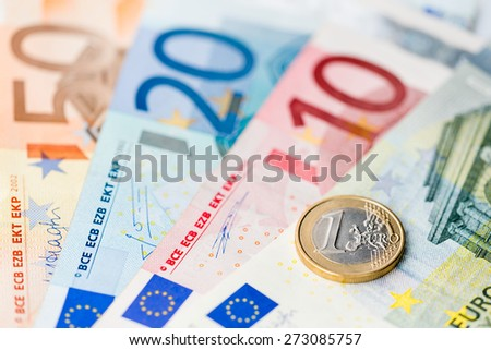 New one Euro coin on Euro banknotes - stock photo