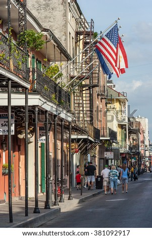 New Orleans, LA/USA - circa March 2009: Old Colonial House with ironwork galleries and american flag on the Streets of French Quarter decorated for Mardi Gras in New Orleans, Louisiana - stock photo