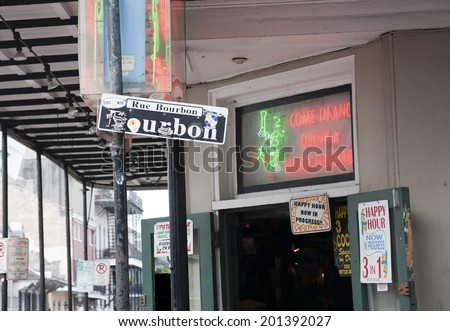 New Orleans, LA, USA - January 25, 2011 : Sign for Bourbon Street surrounded by signs for  Happy Hour specials in the French Quarter in New Orleans Louisiana - stock photo