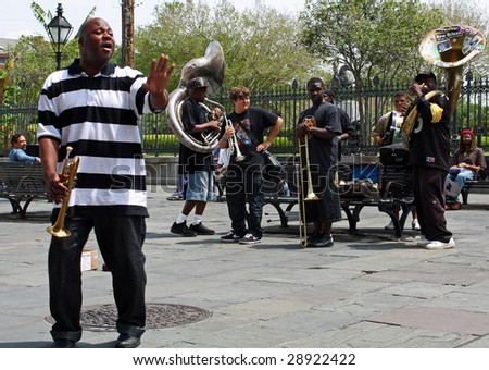 NEW ORLEANS, LOUISIANA - APRIL 13: A jazz band plays in Jackson Square April 13, 2009 in New Orleans, Louisiana after recovery from hurricane Katrina just before the Jazz and Heritage Festival. - stock photo