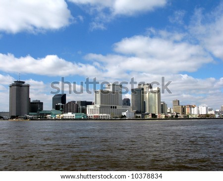New Orleans Louisiana downtown skyline cityscape of the major hotels area and commercial waterfront across the Mississippi River from Algiers on a sunny day with blue sky - stock photo