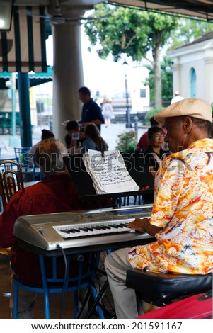 NEW ORLEANS, LOUISIANA, JUNE 24, 2014: Guests dine in an outdoor cafe on Bourbon Street  in New Orleans while they enjoy some local jazz music, June 24, 2014 in New Orleans, Louisiana.  - stock photo