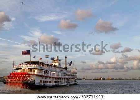 NEW ORLEANS, LOUISIANA, May 4, 2015 : Natchez steamboat leaves the port of New Orleans. Natchez has been the name of several steamboats, and current one has been in operation since 1975. - stock photo