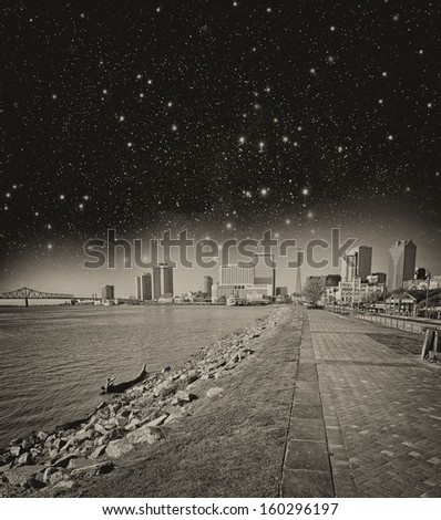 New Orleans, Lousiana. Mississippi waterfront with walkway and city buildings at night. - stock photo