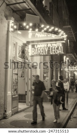 NEW ORLEANS - MARCH 7, 2009: Tourists walk along city streets at night. Almost 9 million people visit New Orleans every year. - stock photo