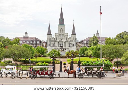 NEW ORLEANS, MISSISSIPPI, USA - MAY 26, 2015: Tourists mingle in Jackson Square, New Orleans, St. Louis Cathedral visible; horse and carriages wait to take people on tours of New Orleans in May 2015. - stock photo