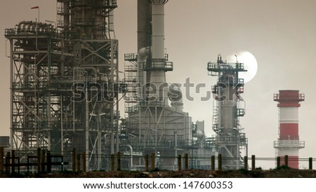 New part still under construction of a major refinery and powerplant in a foggy morning - stock photo