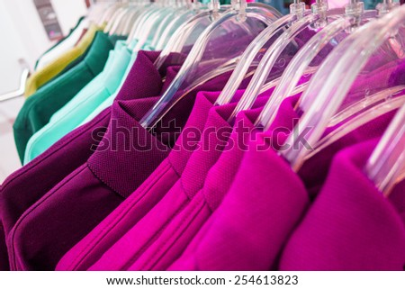 New polo shirts aligned on hangers in fashion store - stock photo