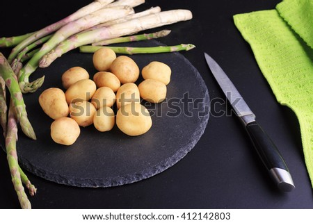 New potatoes and Asparagus on black background. Fresh, raw, organic vegetables. Cooking, Healthy eating concept. - stock photo
