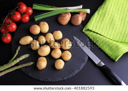 New potatoes, green onion, radishes. Fresh, raw, organic vegetables on black background. Cooking, Healthy eating concept. - stock photo