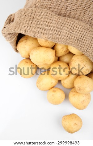 New potatoes in sackcloth bag isolated on white - stock photo