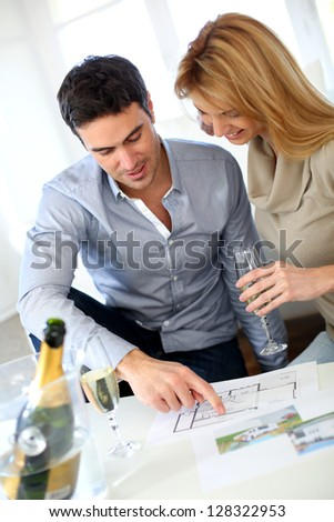 New property owners celebrating with champagne - stock photo