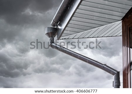 new rain gutter system with drainpipe against dark dramatic sky - stock photo