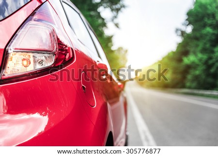 New red car on the road. Travel concept. - stock photo