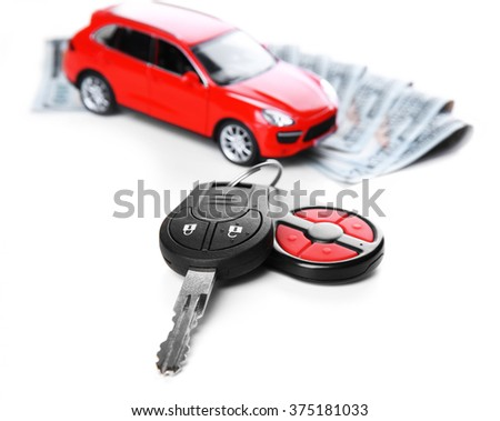 New red car with keys and dollar banknotes on white background - stock photo