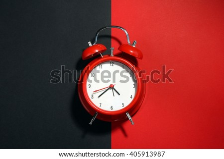 new red clockwork alarm clock on a black and red background - stock photo