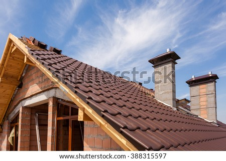 New red tiled Roof with chimneys and skylight - stock photo
